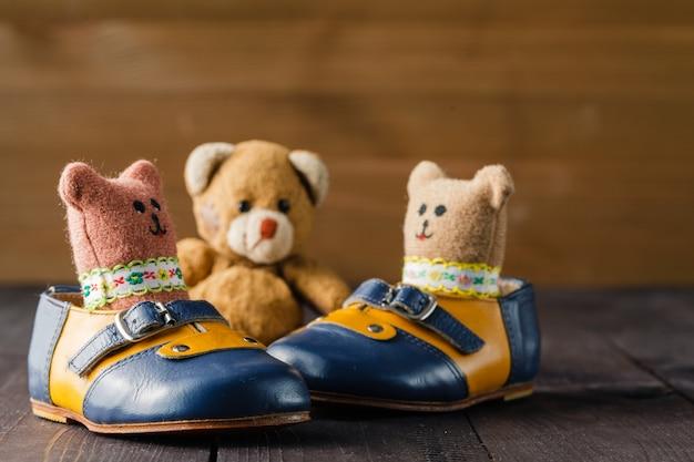 Bottes bébé et poupée jouet sur table en bois