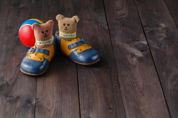 Bottes bébé sur table en bois sur la surface du mur grunge, style vintage