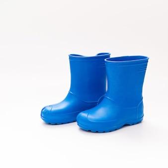 Bottes en caoutchouc bleu sur fond blanc. chaussures pour temps pluvieux et flaques d'eau. magasin de chaussures. protégez vos pieds de l'humidité et de la saleté.