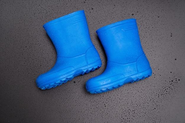 Bottes en caoutchouc bleu sur fond noir. chaussures pour temps pluvieux et flaques d'eau. magasin de chaussures. protégez vos pieds de l'humidité et de la saleté.