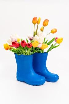 Bottes en caoutchouc bleu avec tulipes multicolores sur fond blanc. chaussures pour temps pluvieux et flaques d'eau. magasin de chaussures. protégez vos pieds de l'humidité et de la saleté.