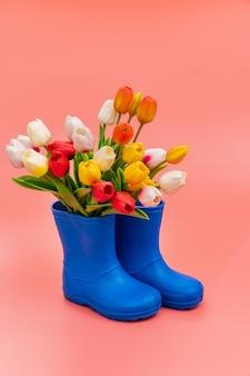 Bottes en caoutchouc bleu avec tulipes multicolores sur fond rose. chaussures pour temps pluvieux et flaques d'eau. magasin de chaussures. protégez vos pieds de l'humidité et de la saleté.