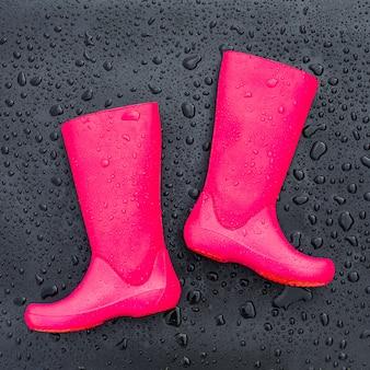 Bottes en caoutchouc rose vif à la mode sur une surface mouillée noire recouverte de gouttes de pluie