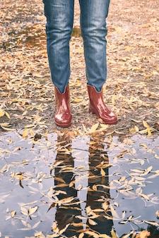 Bottes en caoutchouc rouge devant une flaque d'eau avec des feuilles jaunes en automne