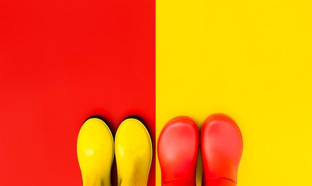 Bottes en caoutchouc rouge sur un fond jaune et bottes jaunes sur un fond rouge se tiennent côte à côte