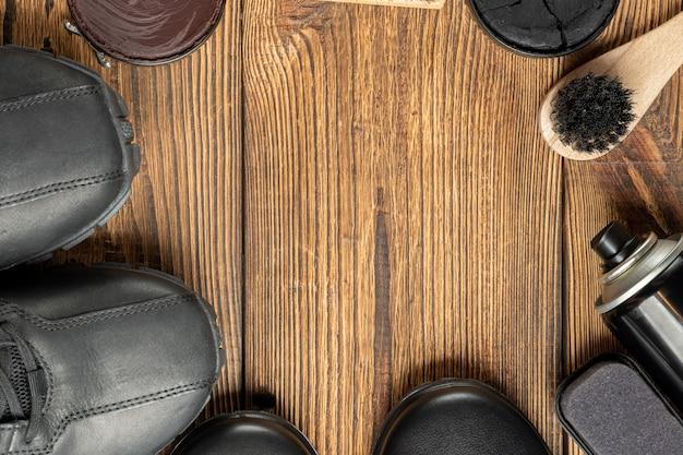 Bottes en cuir, brosses, cire de cirage, produits d'entretien des chaussures sur fond en bois avec espace de copie