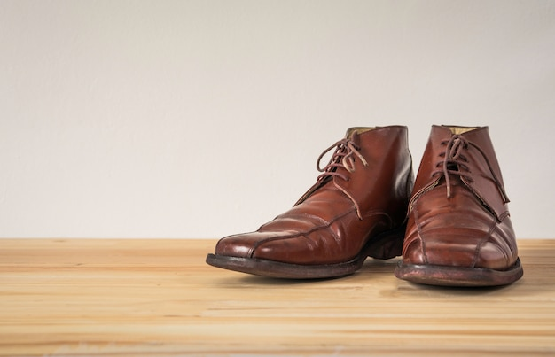 Bottes en cuir marron sur plancher en bois
