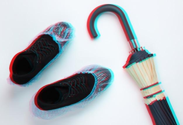 Bottes en daim noir avec couvre-bottes, un parapluie sur fond blanc. vue de dessus. effet glitch. mise à plat