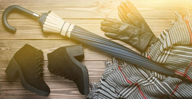 Bottes en daim noir, gants, écharpe, parapluie sur fond de bois. vue de dessus