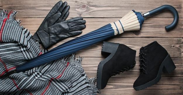 Bottes en daim noir, gants, écharpe, parapluie sur surface en bois