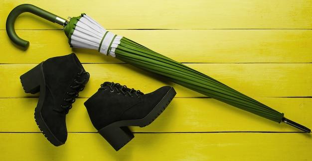 Bottes en daim noir, parapluie sur fond de bois jaune. vue de dessus