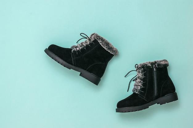 Bottes femmes noires pour l'hiver sur fond bleu. bottes d'hiver élégantes pour femmes. mise à plat.