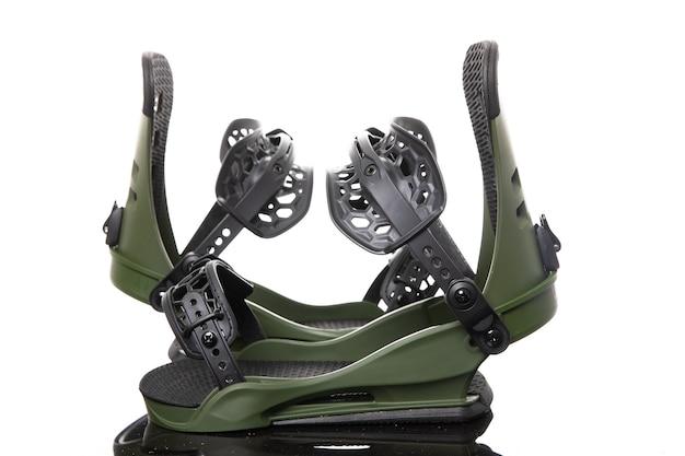 Les bottes de fixation de snowboard se tiennent sur une surface en verre