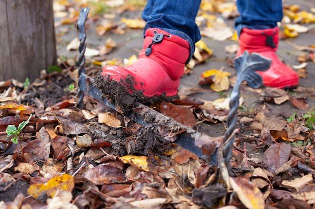 Bottes sur un grattoir à chaussures les bottes en caoutchouc sales sont nettoyées de la saleté de la semelle sur la traditio anglaise...