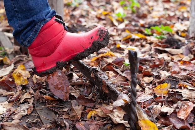 Des bottes en gros plan sur un grattoir à chaussures, des bottes imperméables roses sont nettoyées de la saleté de la semelle sur un angl...