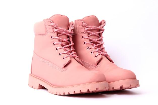 Bottes d'hiver femelles couleur rose isolées sur des chaussures pour femmes blanches
