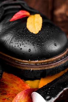 Bottes noires imperméables sur fond en bois avec feuilles d'automne, équipement de polissage, pinceau et crème à polir. macro fermer