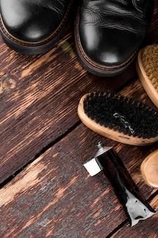 Bottes noires sur une surface en bois avec équipement de polissage, brosser et polir la crème