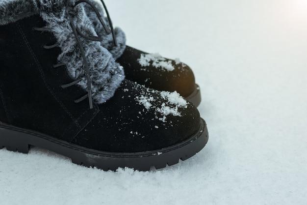 Bottes pour femmes en fourrure dans la neige fraîche. belles et pratiques chaussures d'hiver pour femmes.