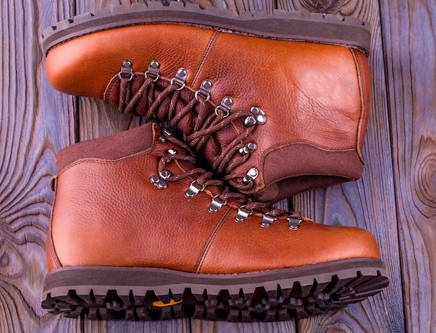 Bottes pour hommes. chaussures d'hiver pour hommes sur un fond en bois.