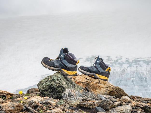 Des bottes de randonnée mouillées sèchent sur une pierre sur fond de hautes montagnes enneigées. les difficultés de la randonnée, le séchage des vêtements dans la nature.