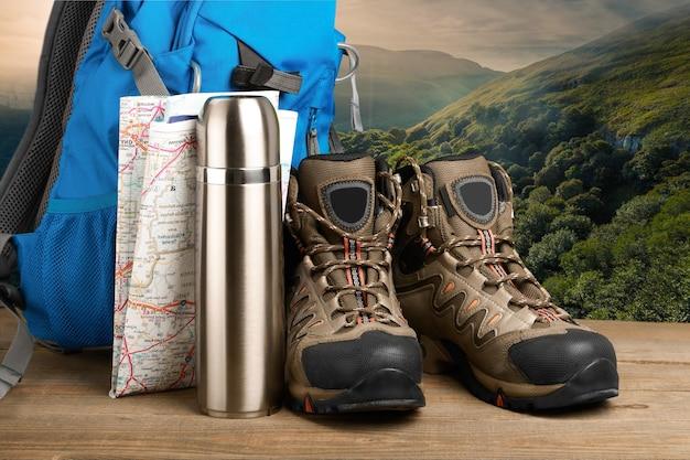 Bottes de randonnée, sac à dos et carte sur fond