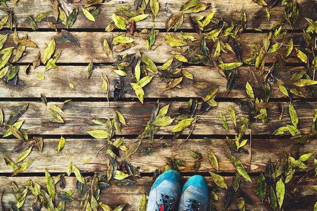 Bottes de randonneurs sur fond de texture en bois du pont avec des feuilles vertes d'automne humides