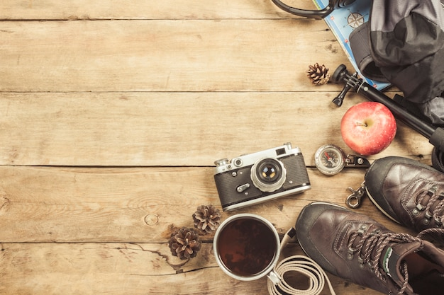 Bottes, sac à dos, boussole et autres équipements de camping sur une surface en bois. le concept de randonnée en montagne ou en forêt, tourisme, repos en tente, camp. mise à plat, vue de dessus.
