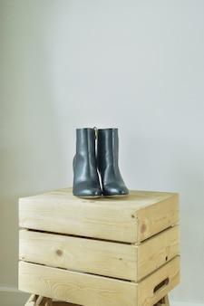 Bottes à talons hauts sur une boîte en bois dans le dressing