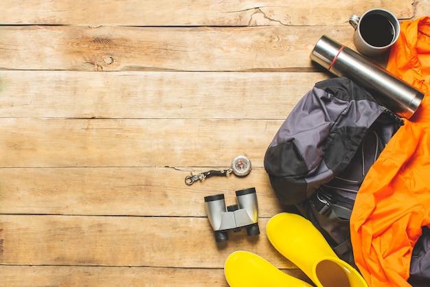 Bottes de trail, jumelles, accessoires de trekking sur fond de bois. concept de randonnée, tourisme, camp, montagnes, forêt.