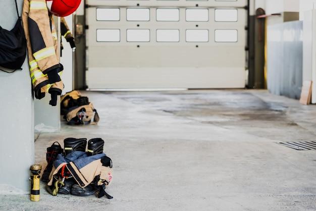 Bottes et veste de pompier sur le plancher du garage d'une caserne de pompiers.