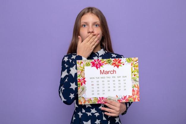 Bouche couverte de peur avec la main belle petite fille le jour de la femme heureuse tenant le calendrier