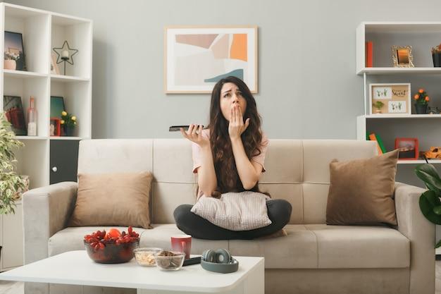 Bouche couverte de regrets avec main jeune fille tenant un téléphone assis sur un canapé derrière une table basse dans le salon