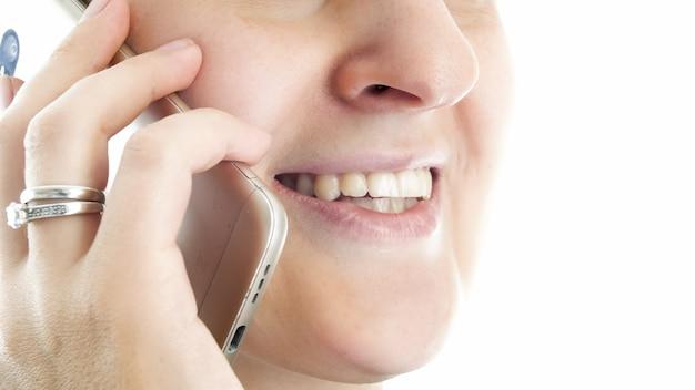 Bouche féminine souriante parlant par téléphone.