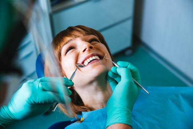 Bouche de femme souriante sous traitement à la clinique dentaire