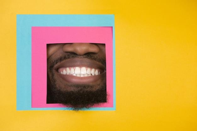 Bouche de l'homme afro-américain jetant un coup d'œil à travers la place en fond jaune