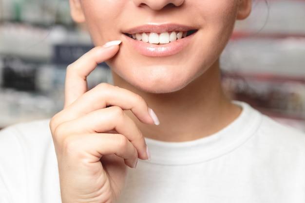 Bouche de modèle féminin avec une peau lisse et parfaite touchant ses lèvres en peluche