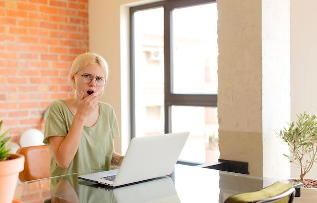 Avec la bouche et les yeux grands ouverts et la main sur le menton, la femme se sentant désagréablement choquée, disant quoi ou wow