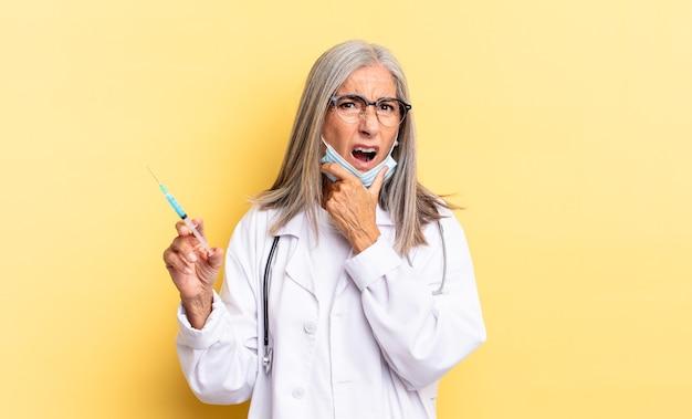 Avec la bouche et les yeux grands ouverts et la main sur le menton, se sentant désagréablement choqué, disant quoi ou wow. concept de médecin et de vaccin