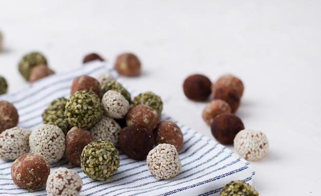 Bouchées énergétiques biologiques avec dattes, graines de citrouille, amande, noix et sésame à la table blanche.