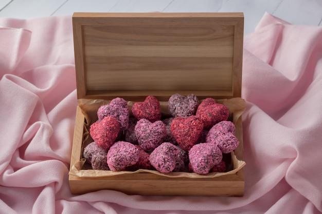Bouchées d'énergie en forme de coeur pour la saint valentin dans une boîte en bois sur un tissu rose, vue de dessus