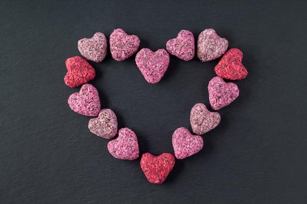 Bouchées d'énergie en forme de coeur pour la saint valentin sur une plaque d'ardoise, mise à plat
