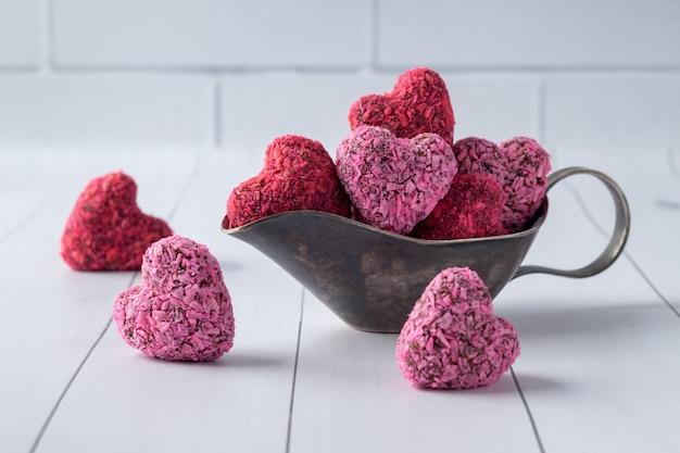 Bouchées d'énergie en forme de coeur pour la saint valentin en saucière sur une table en bois blanc