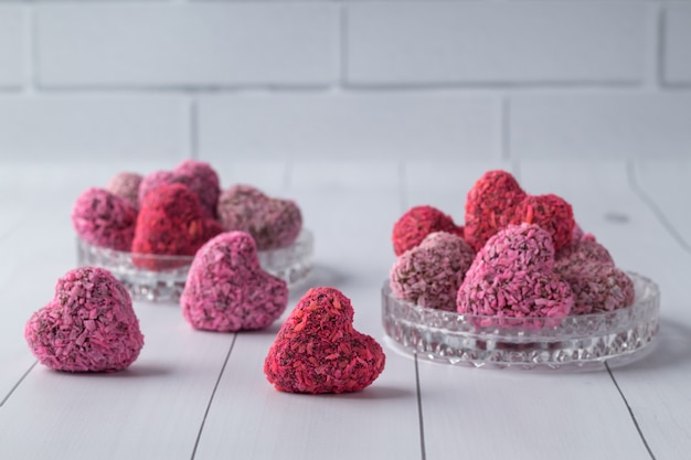 Bouchées d'énergie en forme de coeur pour la saint valentin sur une table en bois blanc