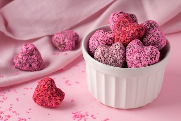 Bouchées d'énergie en forme de coeur pour la saint valentin sur table rose