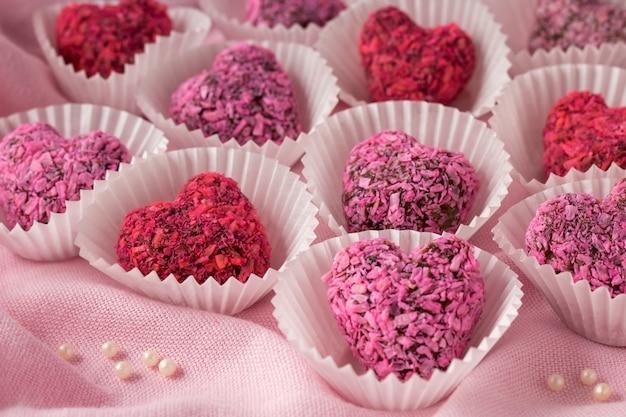 Bouchées d'énergie en forme de coeur pour la saint valentin sur tissu rose