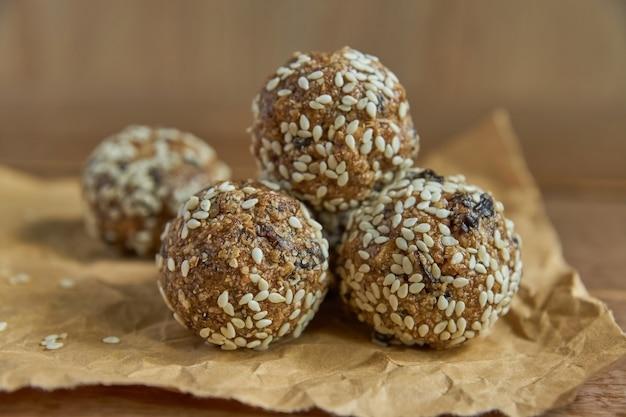 Bouchées de granola bio et saines avec noix, cacao, pruneaux, sésame et miel. collation crue végétalienne et végétarienne sur bois