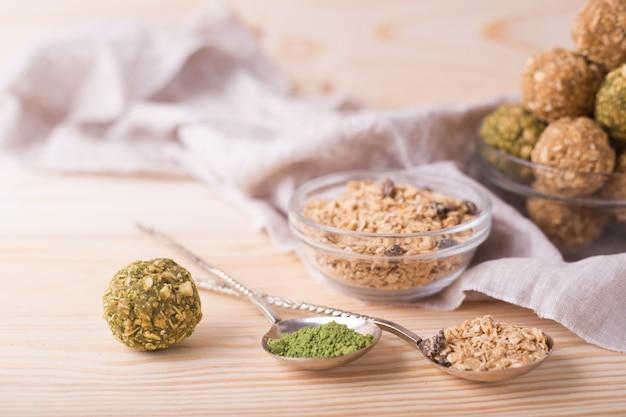 Bouchées de granola bio et saines avec noix, raisins secs, matcha et miel - collation ou repas végétarien cru végétarien