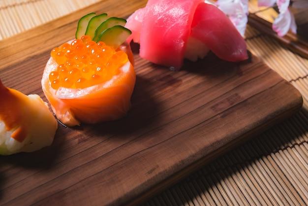 Bouchent Les Aliments Japonais, Ensemble De Sushis Et Pot De Thé Avec Sakura Sur La Table En Bois Photo Premium