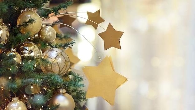 Bouchent arbre de noël décoré de boules dorées et étoiles babiole sur fond de bokeh lumière guirlande pour carte de voeux avec espace pour le texte